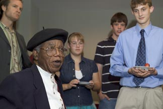 Chinua Achebe talks with the winners of an essay contest