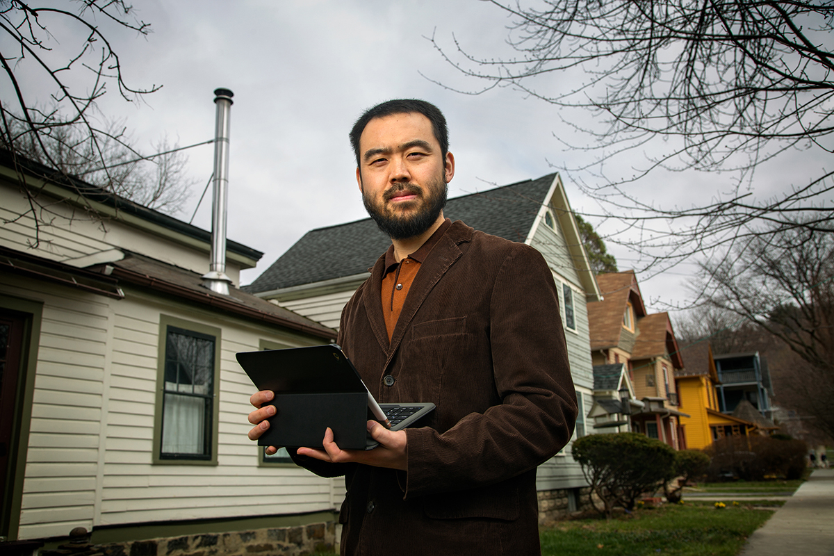 Max Zhang, associate professor of mechanical and aerospace engineering, stands outside a home in the city of Ithaca. Zhang helped the resident of the home to reduce the smoke emanating from the chimney.