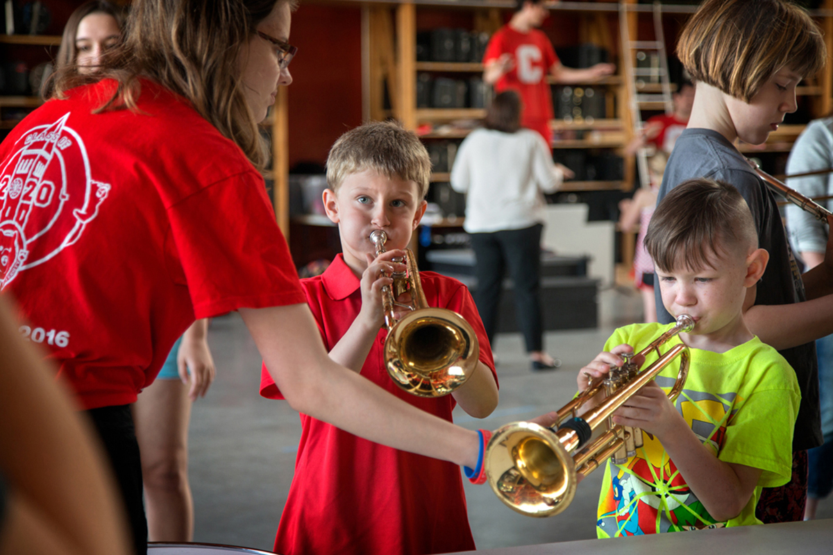 Christian Griep, left, and his cousin Peyton Stewart, give the trumpet a try during a visit with the Big Red Marching Band at the 2017 Bring a Child To Work Day, April 27.