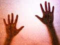 hands behind glass