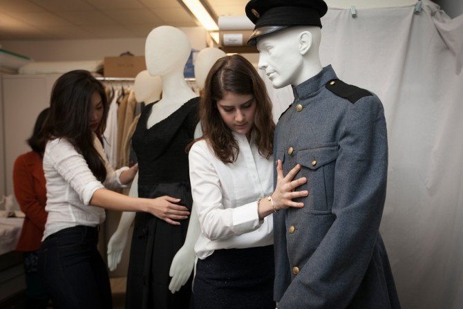 design students dress a mannequin with the Cornell Cadet Corps uniform