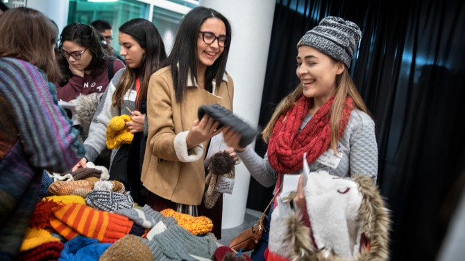 students pick up knitted clothes