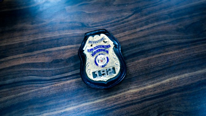 Albany police badge on wooden table