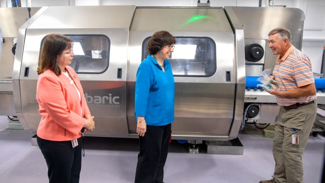 Extension support specialist John Churey, right, discusses the Hiperbaric high-pressure processing unit (HPP) with Olga Padilla-Zakour, professor and chair of the Department of Food Science, left, and President Martha E. Pollack, center
