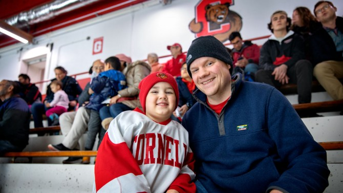 David Winisrski enjoys the hockey game with James during the 2019 Winter Employee Celebration in Lynah Rink.