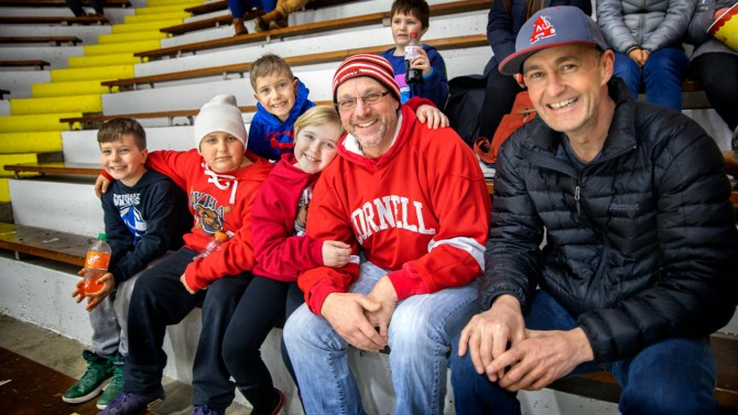 Scott Campbell (far right) and Chris Ford enjoy women's ice hockey with youngsters.