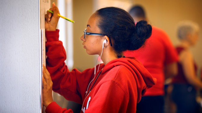 Student in Red Sweatshirt Writing on Paper Attached to Wall