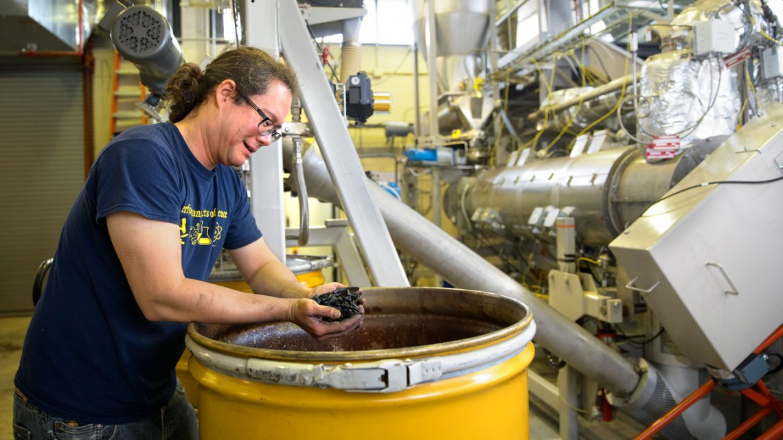 Jason Koski/University Photography Technician Akio Enders examines biochar after it is removed from the the new pyrolysis kiln.
