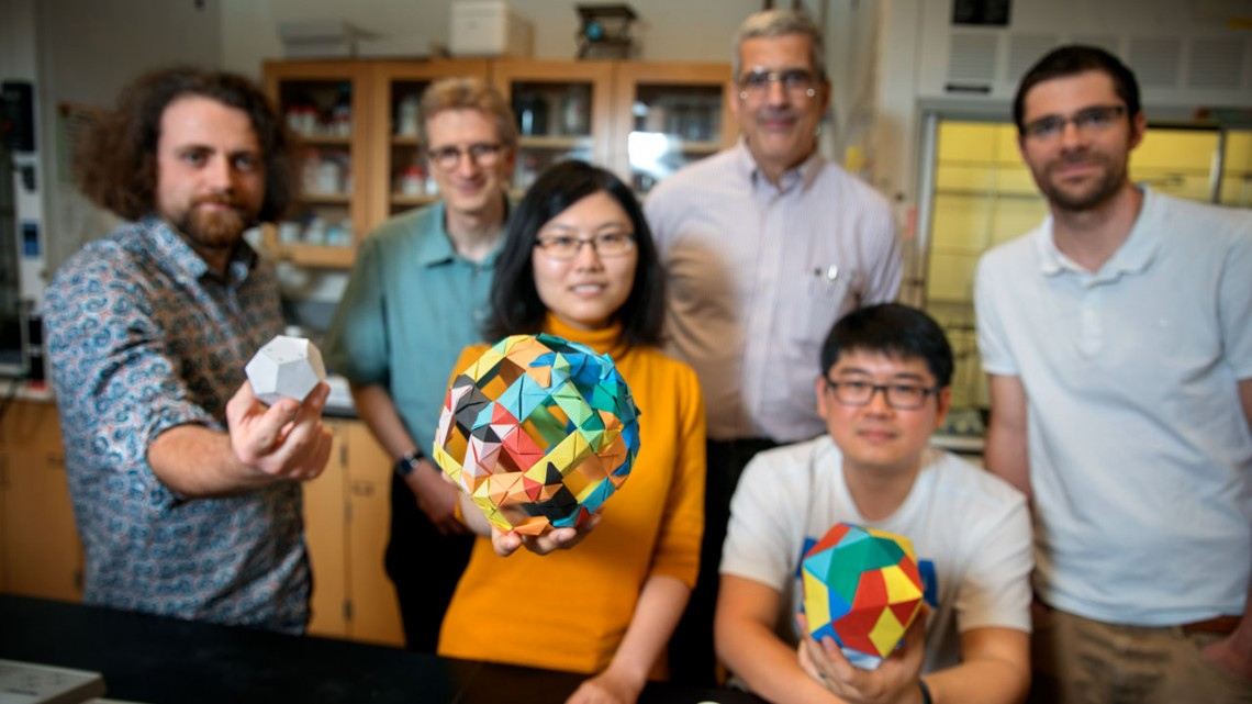 Doctoral student Melik Turker, left, holds a model of a dodecahedron in the lab of Ulrich Wiesner. Also pictured are doctoral student Yunye Gong, center, holding a model of a cage structure, and postdoctoral researcher Kai Ma, holding an icosahedron. The group's paper on their discovery of nanoscale 12-sided silicon cage structures published recently in Nature; in the back row, left-to-right, are Wiesner, engineering professor Peter Doerschuk and postdoc Tangi Aubert.