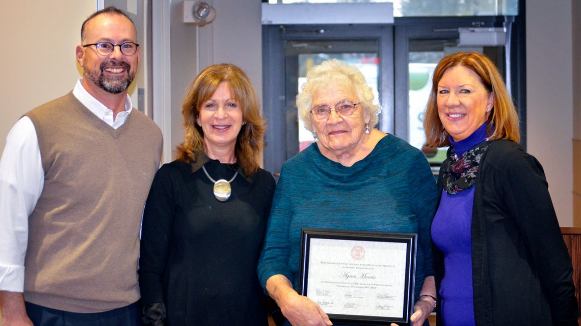 From left: Craig Wiggers, Mary Opperman and (at right) Joanne DeStefano present Agnes Morris with a plaque honoring her with the George Peter Award for Dedicated Service, Nov. 29.