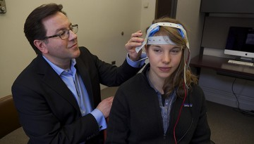 Daniel Casasanto adjusts electrodes on the scalp of a study participant