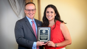 Joel Malina, Cornell vice president for university relations, presents Christa Glazier '01 with the Cornell New York State Hometown Alumni Award