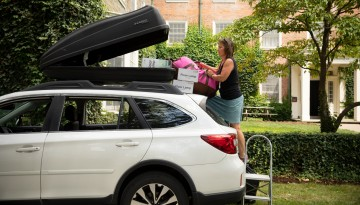 Woman unpacking a car-top carrier.
