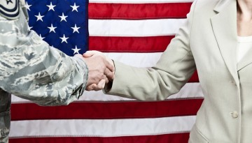 Shaking hands in front of flag