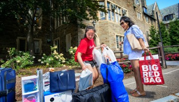 A new student and mother with belongings in front of residence hall on Move-in Day, 2015.