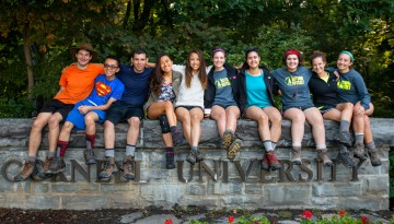 Students sitting on the Cornell University sign wall in 2015.