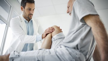 doctor checking man's knee