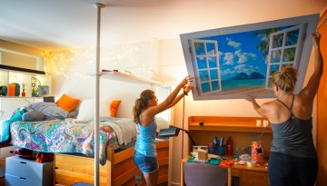 A student hanging a poster in her dorm room, Move-in Day 2015.