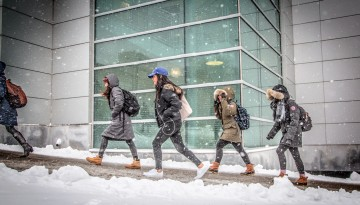 Students walk past Duffield Hall in winter.