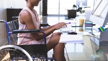 Woman with disability typing at desk