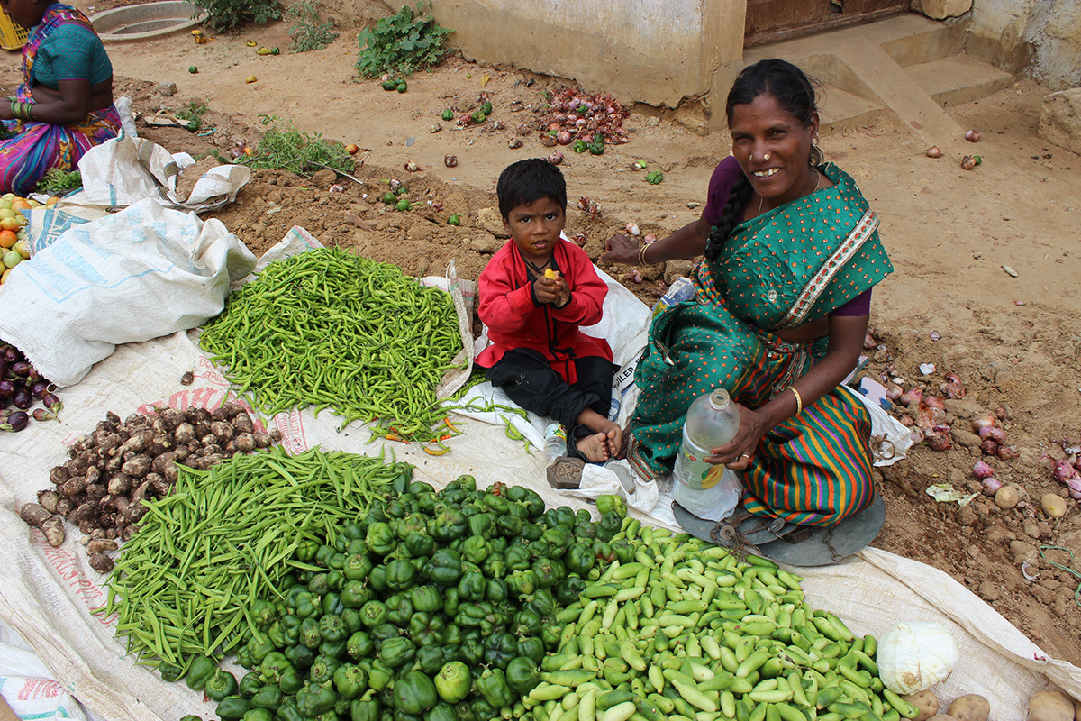 woman in a market in India sells fresh produce