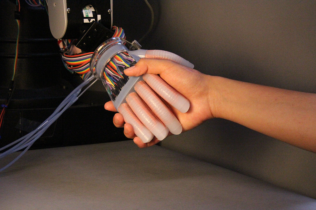 Doctoral student Shuo Li shakes hands with an optoelectronically innervated prosthesis.