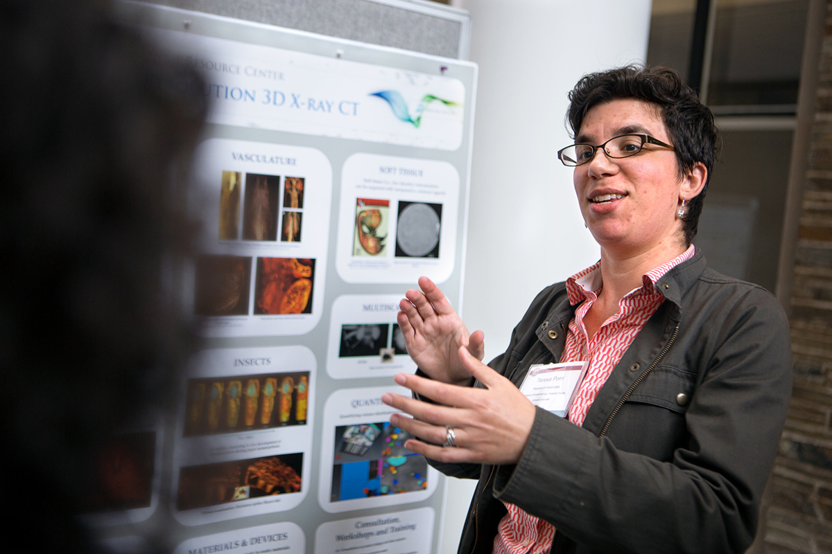 Teresa Porri, CT manager for Cornell's Institute of Biotechnology, discusses her poster illustrating the Biotechnology Resource Center's Imaging Facilities.