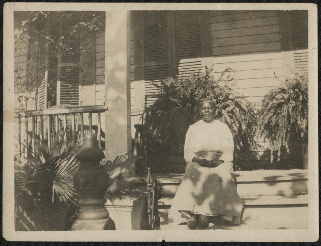 Woman sitting on porch with plants