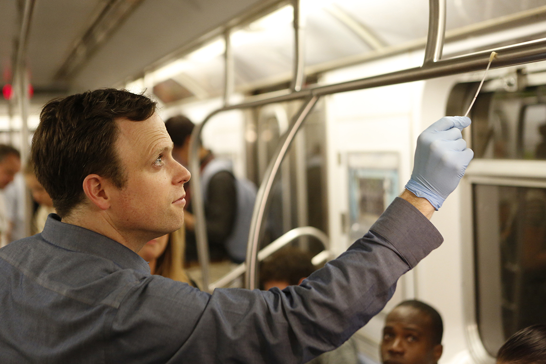 Dr. Christopher Mason swabs a subway car handrail