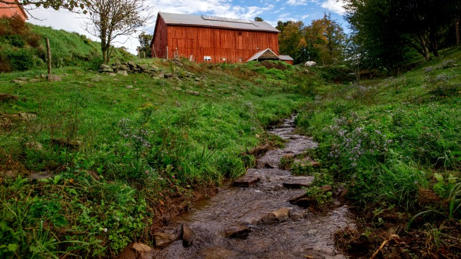A red barn with a brook in the foreground.