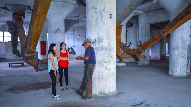 Two students and a man stand in an industrial building