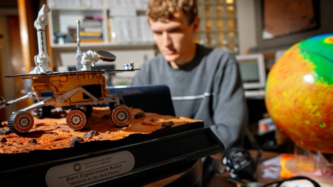 Student works on computer with model of Rover in foreground