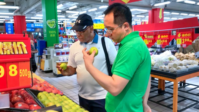 two men inspecing apples at a Chinese grocery store