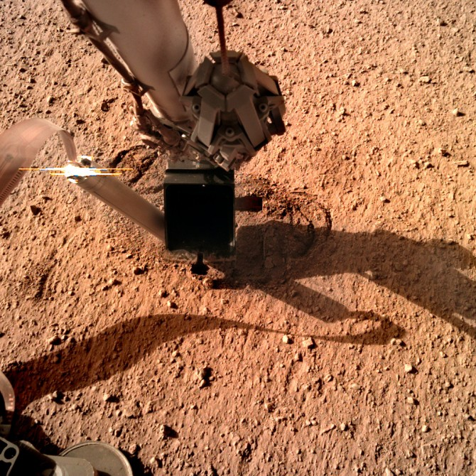 The NASA InSight lander stretches out its robotic arm into the Mars' dusty soil.