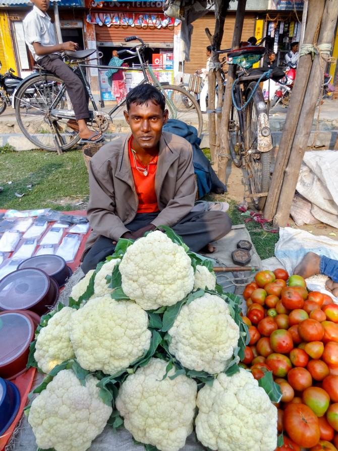man sells cauliflower and tomatoes