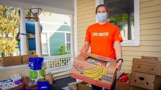 Tompkins County UW volunteer holds box of food