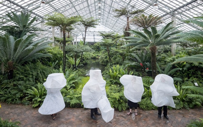A greenhouse with people draped in white net sculptures.