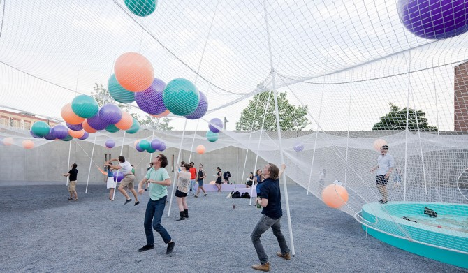 People standing underneath a giant net with colorful balls on top.