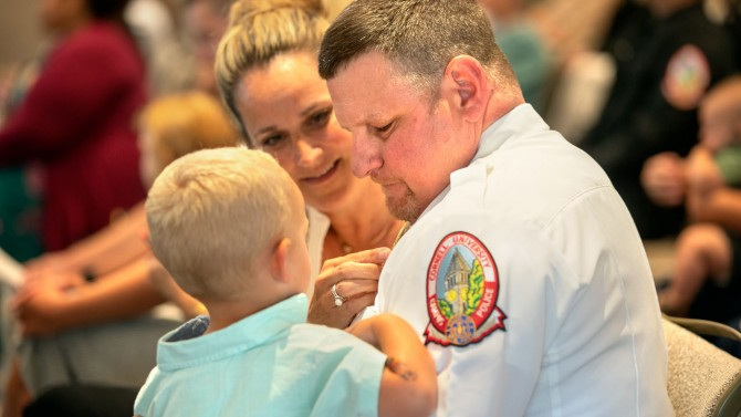 Lt. Jeffery Montesano's wife, Maria, fixes his pin while he holds their grandson at the ceremony.