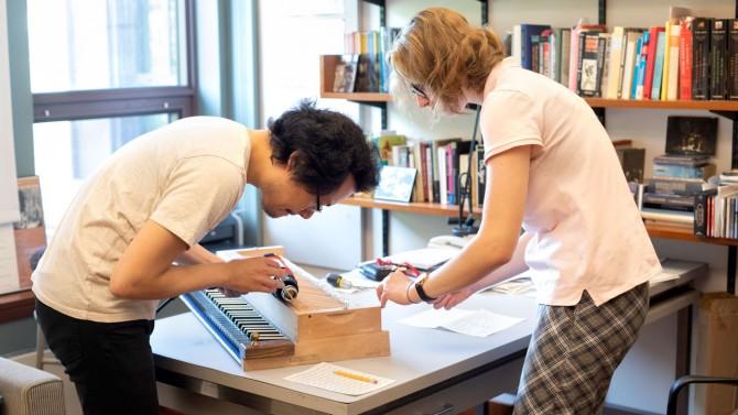 Mike Lee, Ph.D. '15 and Elizaveta Zabelina '24 regulate a piano