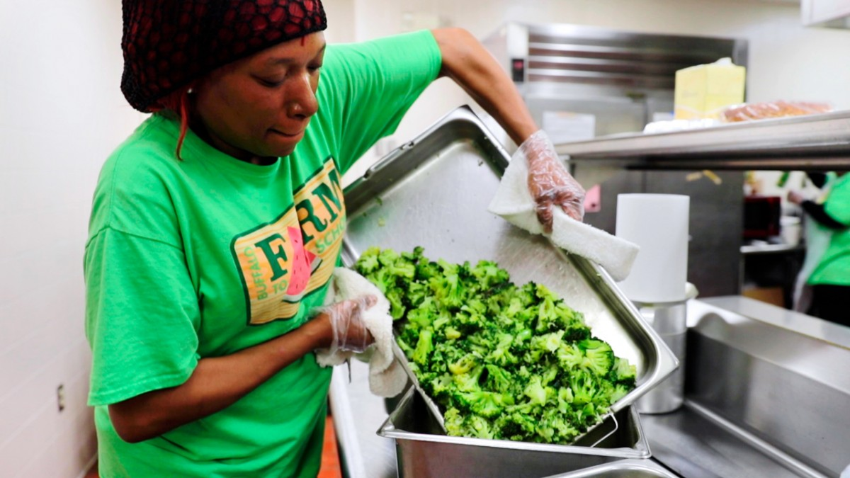 Selema Harris, a food service employee at City Honors School in Buffalo, New York, prepares locally-grown broccoli for the school's lunch.