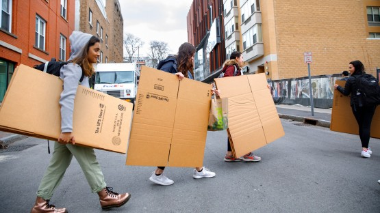 Students carry boxes through Collegetown