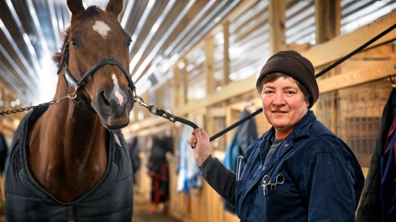 Dr. Barbara Mix, DVM '82, stops by a stable near Horseheads, New York, to check on an injured show horse