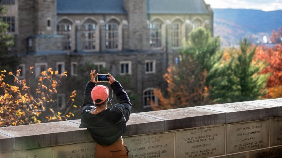 A student pauses to take a photo of the sunset from the Founders Wall outside Uris Library.