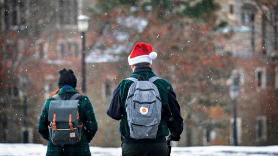 Students walk across Ho Plaza as a light snow falls.