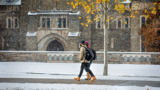 Students pass Myron Taylor Hall as November snow hangs in the air.