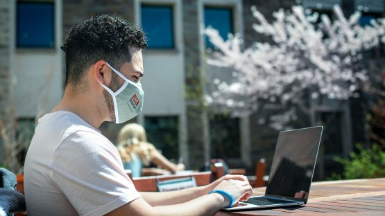 A student works in the courtyard of Ives Hall.