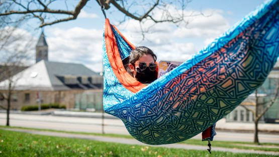 A student studies in a hammock on the hillside above Klarman Hall.