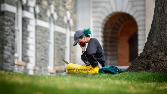 A student works in the grass outside Sibley Hall.