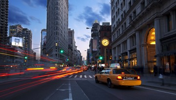 New York City street scene in the evening with a tax in the foreground.